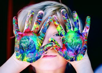 child holding up painted hands