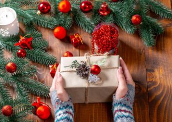 Simple holiday gift in womans hands with holiday decor