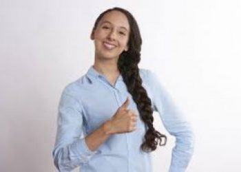 woman showing self confidence by smiling and giving a thumbs up
