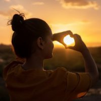 woman looking at sunset through hand heart sign