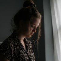 sad woman standing by window