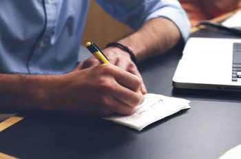 """""""man writing in notebook, creating an action plan for potential life changes of covid-19"""""""